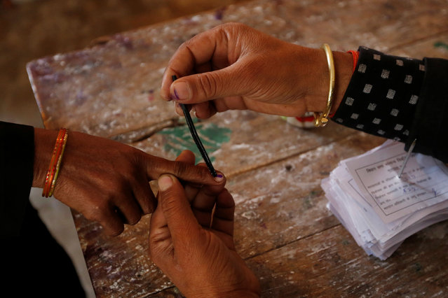 A woman gets her finger inked before casting her vote at a polling station during the state assembly election in Hapur, in the central state of Uttar Pradesh, India, February 11, 2017. (Photo by Adnan Abidi/Reuters)