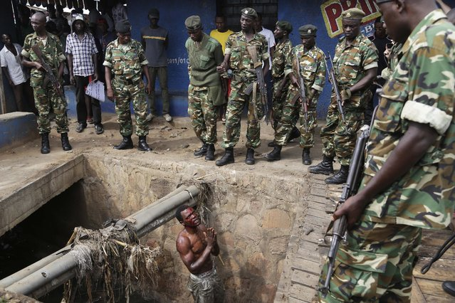 Jean Claude Niyonzima, a suspected member of the ruling party's Imbonerakure youth militia, pleads with soldiers to protect him from a mob of demonstrators after he came out of hiding in a sewer in the Cibitoke  district of Bujumbura, Burundi, Thursday May 7, 2015.  (Photo by Jerome Delay/AP Photo)