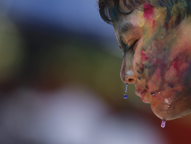 Myanmar Hindu boy smeared in colors as he takes part the Holi festival celebrations in Yangon, Myanmar, 23 March 2016. Holi is celebrated at the end of the winter season on the last full moon day of the lunar month Phalguna (February or March) in Hindu calendar which usually falls in the later part of February or March and is celebrated by people throwing colored powder and colored water at each other. (Photo by Lynn Bo Bo/EPA)