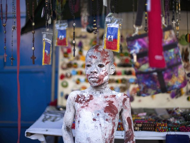 A youth with his body painted attends Carnival celebrations in Jacmel, Haiti, Sunday, February 23, 2014. The youth is painted in the likeness of an indigenous person from the island of Hispaniola from centuries ago. (Photo by Dieu Nalio Chery/AP Photo)