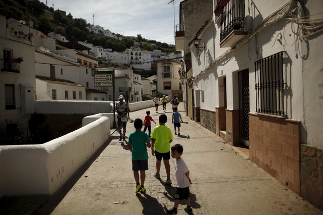Children watch as runners participate in the XVIII 101km international competition in Setenil de las Bodegas, southern Spain, May 9, 2015. (Photo by Jon Nazca/Reuters)
