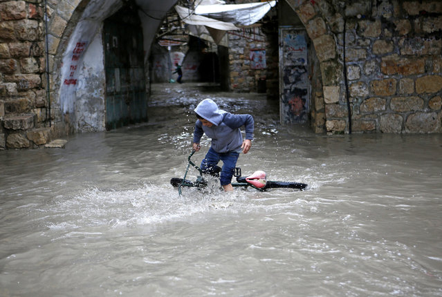 A Palestinian boy tries to ride his bicycle through flood water following heavy rain in the in the old city of West Bank town Hebron, 28 March 2016. (Photo by Abed Al Hashlamoun/EPA)