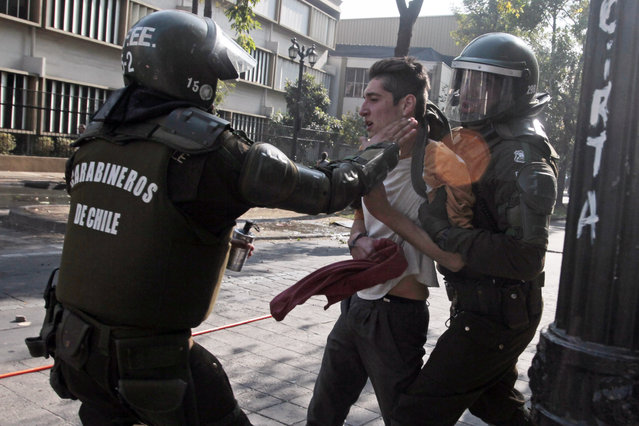 A protester is detained by the police during clashes during a student demonstration in Santiago, Chile, Thursday, May 14, 2015. (Photo by Luis Hidalgo/AP Photo)