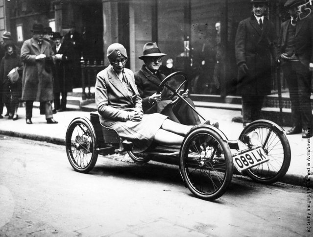 1929: A man and a woman riding in an Auto Red Bug, America's latest electric 2-seater runabout, in a London street