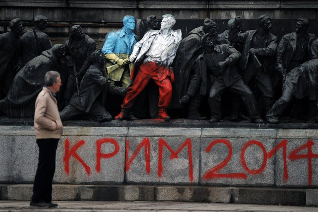"""A man looks at the figures of Communist soldiers painted in the colours of the Ukranian and Polish flags by an unknown artist with the sign """"Crimea 2014"""" in central Sofia on March 5, 2014. The monument was painted overnight in Ukrainian and Polish national flag colours together with texts reading """"Crimea 2014"""", """"Katyn 5.03.1940"""" and """"Putin go home!"""" (Photo by Nikolay Doychinov/AFP Photo)"""