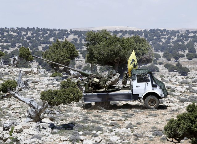 Lebanon's Hezbollah fighters rest on the back of a pick-up truck with an installed weapon in Khashaat, in the Qalamoun region after they advanced in the area May 15, 2015. Lebanon's Hezbollah and Syria's army made big advances against insurgents in mountains north of Damascus on Wednesday, Hezbollah and Syrian state media said, shoring up President Bashar al-Assad's grip on the border zone. (Photo by Mohamed Azakir/Reuters)