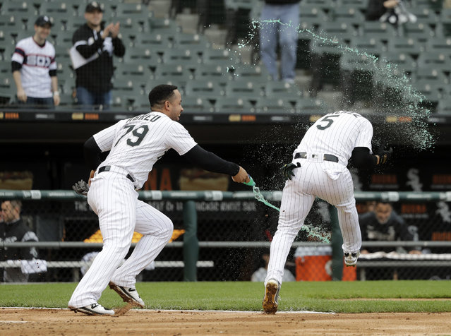 Chicago White Sox's Jose Abreu, left, splashes teammate Yolmer Sanchez after Sanchez's RBI-single off Kansas City Royals relief pitcher Kevin McCarthy won the contest in the ninth inning of a baseball game that was suspended due to rain the previous day, in Chicago, Tuesday, May 28, 2019. The White Sox won 2-1. (Photo by Charles Rex Arbogast/AP Photo)