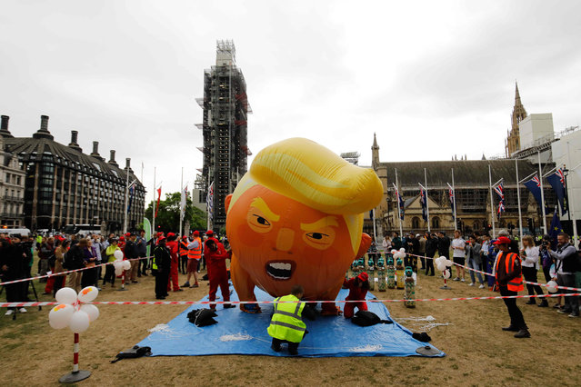 Anti-Trump demonstrators inflate a giant balloon depicting US President Donald Trump as an orange baby in Parliament Square in London on June 4, 2019, on the second day of Trump's three-day State Visit to the UK. US President Donald Trump turns from pomp and ceremony to politics and business on Tuesday as he meets Prime Minister Theresa May on the second day of a state visit expected to be accompanied by mass protests. (Photo by Tolga Akmen/AFP Photo)