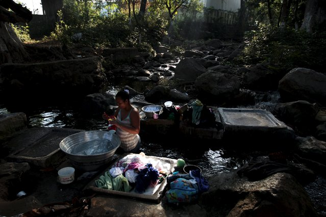 Women wash their clothes at Las Tres Piedras river in Nejapa, El Salvador February 23, 2016. The El Salvador government has issued an alert due to water shortage, attributed to climate change. (Photo by Jose Cabezas/Reuters)