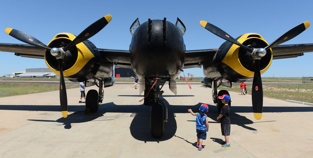 Phillip Williams, left, and Finlay Patterson, both of Odessa, Texas, look the B-26 aircraft on display during the Memorial Day observance at Midland International Air and Spaceport, Monday, May 25, 2015, in Midland, Texas. (Photo by Mark Sterkel/Odessa American via AP Photo)