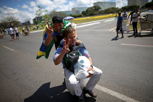 People gesture while riding on a box with wheels in Brasilia, Brazil April 17, 2016. (Photo by Adriano Machado/Reuters)