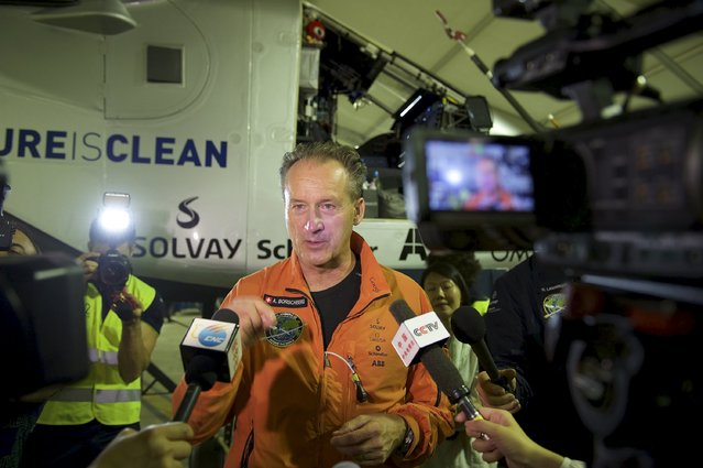 Swiss pilot Andre Boschberg (C) speaks during an interview in front of the Solar Impulse 2 plane before taking off at the Nanjing Lukou International Airport, Jiangsu province, China, May 30, 2015. The plane took off from eastern China's Nanjing after more than a month of delay to complete the most challenging leg yet of its Round The World adventure: the crossing of the Pacific via Hawaii. Pilots Piccard and Borschberg will take turns at the controls of Solar Impulse 2, which began its journey in Abu Dhabi in the United Arab Emirates on March 9, as it makes its way in the first round-the-world solar-powered flight in about 25 flight days at speeds of between 50 kph and 100 kph (30 mph to 60 mph). Picture taken May 30, 2015. REUTERS/Stringer