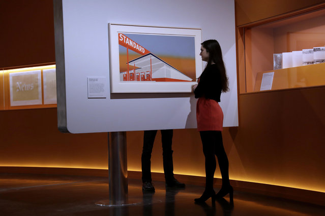 "British Museum representatives pose for photographs in front of and behind ""Standard Station"" by Edward Ruscha which features in ""The American Dream: pop to the present"" exhibition during a media photocall at the British Museum in London, Monday, March 6, 2017. (Photo by Matt Dunham/AP Photo)"