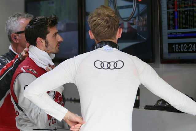 Italian driver of the Audi R18 E-TRON Quattro No9 Marco Bonnanomi, left, talks with teammate German driver Rene Rast as they watch a TV screen during the 83rd 24-hour Le Mans endurance race, in Le Mans, western France, Saturday, June 13, 2015. (AP Photo/David Vincent)