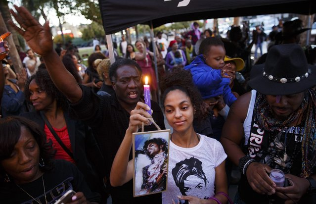 Mourners pay tribute to musician Prince during a vigil in Los Angeles, California, 21 April 2016. American singer-songwriter and musician Prince, a multi-talented artist who produced a string of genre-fusing hits in the 1980s, died on 21 April at his residence in Chanhassen, Minnesota. He was 57. (Photo by Eugene Garcia/EPA)