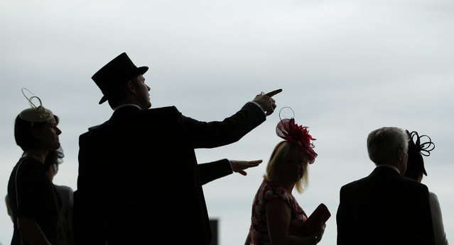 Race goers gesture in the Royal Enclosure on the second day of the Royal Ascot horse racing meet at Ascot, England, Wednesday, June 17, 2015. Royal Ascot is the annual five day horse race meeting that Britain's Queen Elizabeth II attends every day of the event.(AP Photo/Alastair Grant)