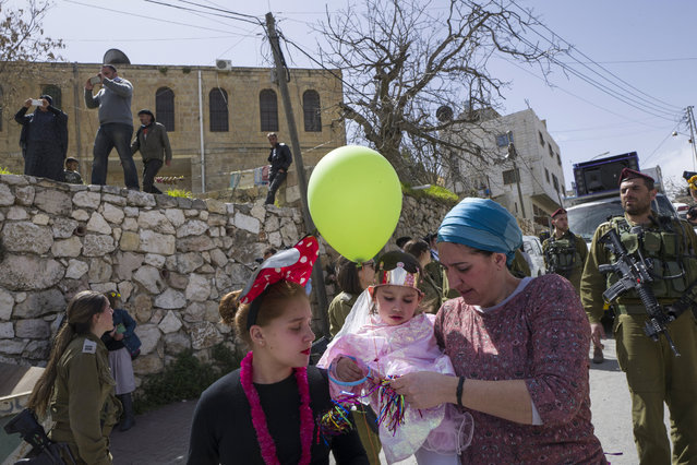 A Palestinian family watches from their house as Jews pass by, guarded by Israeli soldiers, during the annual Purim parade in the predominantly Jewish sector of the West Bank city of Hebron, 12 March 2017. (Photo by Jim Hollander/EPA)
