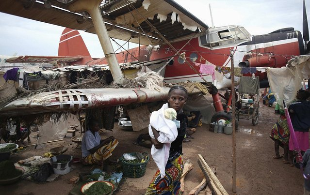 Living amongst old and wrecked airplanes, an internally displaced woman carries her child in a camp for internally displaced people at Bangui International Airport, Central African Republic, on April 10, 2014. (Photo by Goran Tomasevic/Reuters)