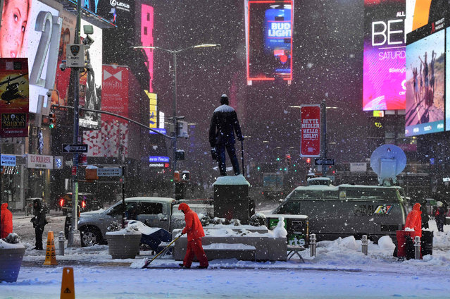 Men plow snow in Times Square during a snowstorm in New York on March 14, 2017. (Photo by Jewel Samad/AFP Photo)
