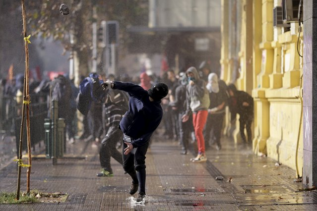 A protester hurls a stone at police during a demonstration to demand changes in the Chilean education system in Santiago, Chile June 25, 2015. (Photo by Ueslei Marcelino/Reuters)