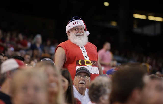 A fan watches a replay during the annual Christmas in June event at a baseball game between the Los Angeles Angels and the Seattle Mariners, Friday, June 26, 2015, in Anaheim, Calif. (Зрщещ ин Jae C. Hong/AP Photo)