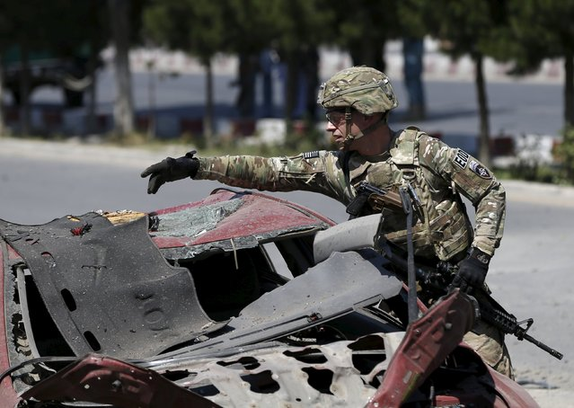 A U.S. soldier inspects the site of a suicide bomb attack in Kabul, Afghanistan, June 30, 2015. (Photo by Omar Sobhani/Reuters)