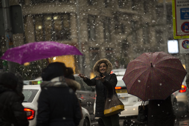 A woman tries to catch snowflakes in main Gran Via avenue in central Madrid, Thursday, March 23, 2017. A polar wind is crossing Spain as many parts of the north of the country registered freezing temperatures, snow and cold wind marking the beginning of the spring. (Photo by Francisco Seco/AP Photo)