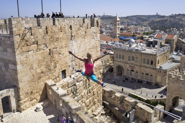 Heather Larsen from Golden, Colorado, USA performs a split while walking the slackfline or highline across two towers in the Tower of David citadel complex overlooking the Old City of Jerusalem 02 May 2016. Larsen is one of the world's top female highliners, or slack liners and walked the lines as part of a Kickstarter campaign for an outdoor product. The tower at left was built by King King Herod some 2000 years ago. (Photo by Jim Hollander/EPA)