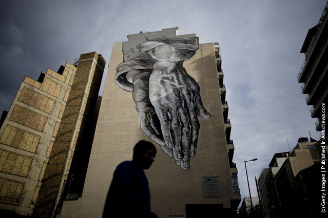 A man walks past graffiti displayed on a building on December 6, 2011 in Athens, Greece