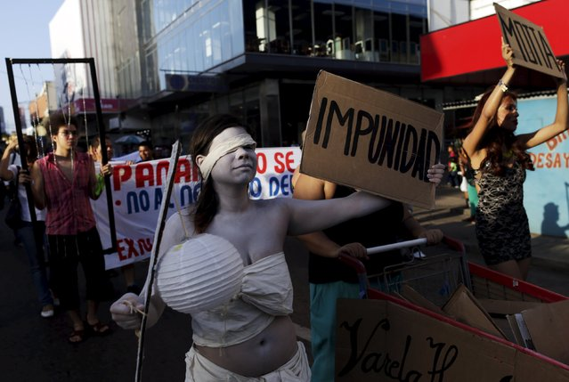 """A protesters hold placards and banners during an anti-corruption march in Panama City July 1, 2015. Activist groups took part on Wednesday in a protest against the alleged corruption cases involving members of former president Ricardo Martinelli's administration, according to local media. The placard reads """"Impunity"""". (Photo by Carlos Jasso/Reuters)"""