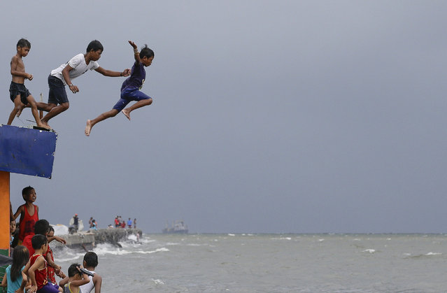 Boys jump into the water despite strong waves after a strong downpour at Manila's bay, Philippines, Wednesday, July 17, 2019. Schools in metropolitan Manila have been suspended as Tropical Storm Danas, locally named Falcon, continue to enhance the southwest monsoon as it maintains its strength bringing heavy rains over parts of Luzon and Visayas according to the Philippine Atmospheric Geophysical and Astronomical Services Administration. (Photo by Aaron Favila/AP Photo)