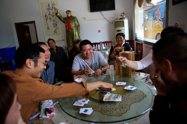 Chinese visitors play a card game in a restaurant where a Mao Zedong statue overlooks them in the background in Shaoshan, Hunan Province in central China, 28 April 2016. (Photo by How Hwee Young/EPA)