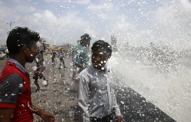 People get drenched in a wave hitting the shore during high tide at the Arabian sea promenade in Mumbai, India, Sunday, July 5, 2015. (Photo by Rafiq Maqbool/AP Photo)