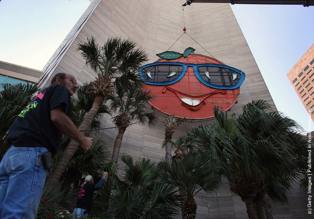 Bill Flaherty from Mr. Neon inc. helps place the Big Orange New Years time ball onto the side of the Hotel InterContinental on December 28, 2011 in Miami, Florida. The 35-foot ball rises 400 feet to the top of the building and is lowered at midnight on the 31st to mark the beginning of the New Year in Miami