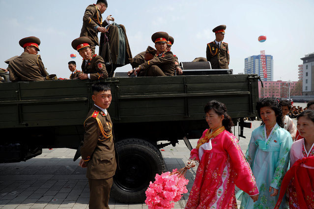 Women in traditional clothes walk past military band members getting onto a truck after a military parade marking the 105th birth anniversary of North Korea's founding father, Kim Il Sung in Pyongyang, April 15, 2017. Covering a North Korean military parade is an emotional roller coaster. Foreign journalists stand just metres from the action in Pyongyang's Kim Il Sung Square. The ground at your feet shakes as tanks rumble past, leaving a diesel aftertaste in your mouth. That heavy equipment, and the brigades of tightly coordinated goose-stepping soldiers that come before them, are an impressive sight. (Photo by Damir Sagolj/Reuters)