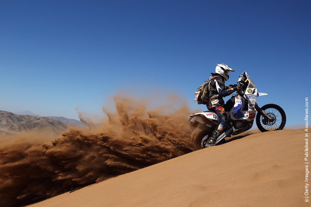 Neil Scott Williams of South Africa and the Memo-Tours Alfie Cox Team rides up a sand dune during stage seven of the 2012 Dakar Rally