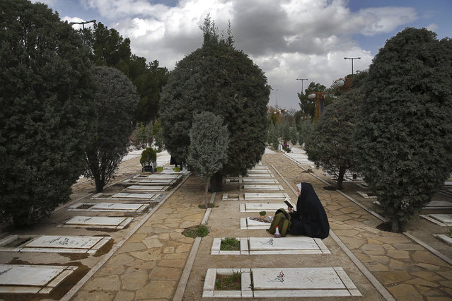 """An Iranian woman prays at the graves of unknown soldiers who were killed during 1980-88 Iran-Iraq war, at the Behesht-e-Zahra cemetery just outside Tehran, Iran, Monday, March 20, 2017, on the eve of the Iranian New Year, or Nowruz. Nowruz which means """"New Day"""" in Persian, marks the first day of spring and the beginning of the year on the Iranian calendar, which occurs exactly on the Spring Equinox. (Photo by Ebrahim Noroozi/AP Photo)"""