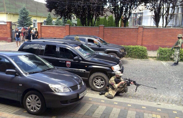 Armed activists of the nationalist militia Right Sector  take position in the site of unrest in Mukhachevo, Western Ukraine,  Saturday, July 11, 2015. At least two people were killed Saturday in a gun and grenade attack in a western Ukraine city involving the country's notorious nationalist militia Right Sector. (Photo by AP Photo)