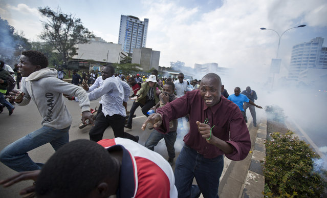 Opposition supporters, some carrying rocks, flee from clouds of tear gas fired by riot police, during a protest in downtown Nairobi, Kenya Monday, May 16, 2016. Kenyan police have tear-gassed and beaten opposition supporters during a protest demanding the disbandment of the electoral authority over alleged bias and corruption. (Photo by Ben Curtis/AP Photo)
