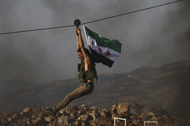 In this Monday October 7, 2019 photo, a Turkish-backed fighter from the Free Syrian Army, exercises with his group's  flag during military training in preparation for an anticipated Turkish incursion targeting Syrian Kurdish fighters, near Azaz, in north Syria. Turkey's vice president said Tuesday his country won't bow to threats in an apparent response to U.S. President Donald Trump who warned Ankara about the scope of its planned military incursion into northeast Syria. (Photo by AP Photo)