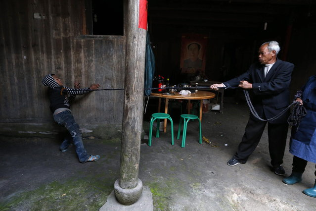Xie Guobiao (L), 11, attempts to walk away while being tied up by a rope held by his grandfather at his home in Daohui village of Lishui, Zhejiang province May 7, 2014. (Photo by William Hong/Reuters)