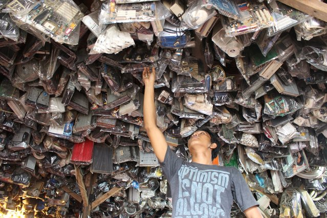 A man looks for used computer motherboards at a market in Depok, Indonesia, 12 May 2014. According to a report by the World Bank, Indonesia has become the world's tenth largest economy. Indonesia's economy grew 5.21 percent in the first quarter of this year, the slowest pace in more than four years, the government said. (Photo by Adi Weda/EPA)