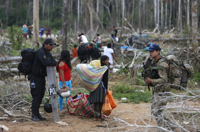 Miners and their families leave a camp after Peruvian police operation to destroy illegal gold mining camps in a zone known as Mega 14, in the southern Amazon region of Madre de Dios July 14, 2015. (Photo by Janine Costa/Reuters)