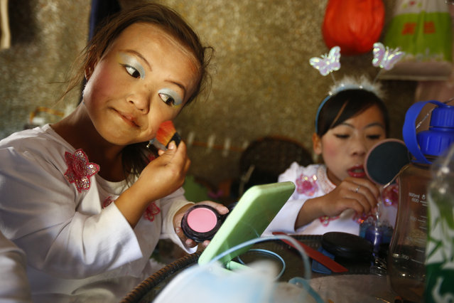 """""""Dwarf Empire"""" cast members 19-year-old Han Zhen Yan (L) and 19-year-old Peng Chun Song apply make up backstage before going to perform at the Dwarf Empire theme park outside Kunming, China's Yunnan province, 04 April 2013. (Photo by Diego Azubel/EPA)"""