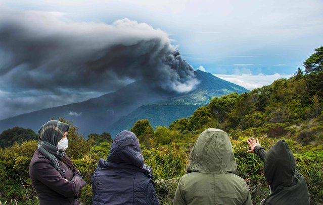 People look at the Turrialba volcano as it spewes ashes on May 20, 2016, in Cartago, Costa Rica. The Turrialba volcano started erupting columns of smoke and ash that the wind extended towards the Costa Rican capital, in what according to experts is the strongest eruption in the past six years. (Photo by Ezequiel Becerra/AFP Photo)