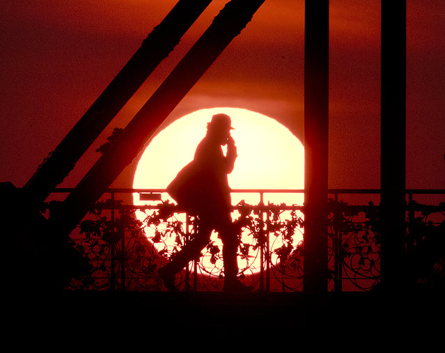 "The sun rises behind the ""Eiserne Steg"" (Iron Footbridge) pedestrian bridge in Frankfurt, Germany, early Tuesday, April 2, 2019. (Photo by Michael Probst/AP Photo)"