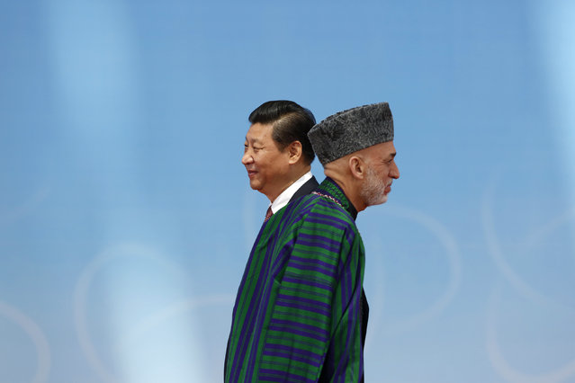 Afghan President Hamid Karzai (R) walks away after shaking hands with his Chinese counterpart Xi Jinping before the opening ceremony in the Expo Center during the fourth Conference on Interaction and Confidence Building Measures in Asia (CICA) summit in Shanghai May 21, 2014. (Photo by Aly Song/Reuters)