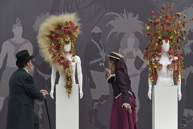 Exhibitors wearing victorian costumes pose as they view floral designed headwear at Chelsea Flower Show in London, Britain, May 23, 2016. (Photo by Toby Melville/Reuters)