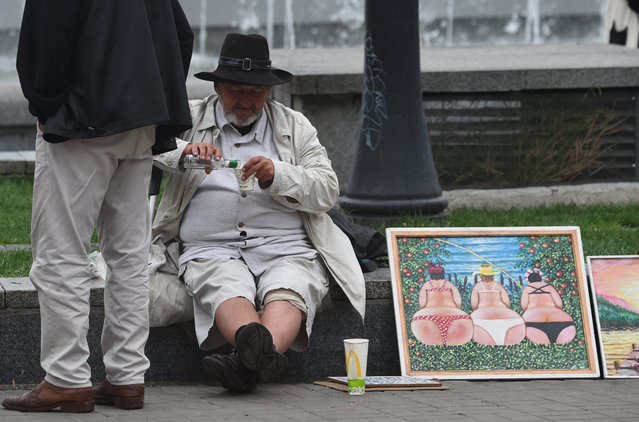 A street artist drinks vodka as he sells his paintings to tourists in the center of Ukrainian capital of Kiev, on August 16, 2019. (Photo by Sergei Supinsky/AFP Photo)