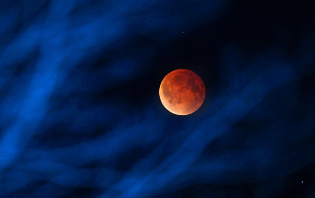 The moon glows a red hue during a total lunar eclipse Tuesday, April 15, 2014, as seen from the Milwaukee area. Tuesday's eclipse is the first of four total lunar eclipses that will take place between 2014 to 2015. (Photo by Mike De Sisti/AP Photo/Milwaukee Journal-Sentinel)